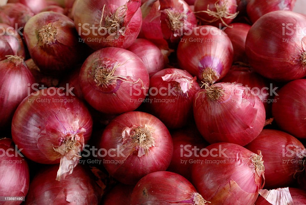 A pile of red onions as a background stock photo