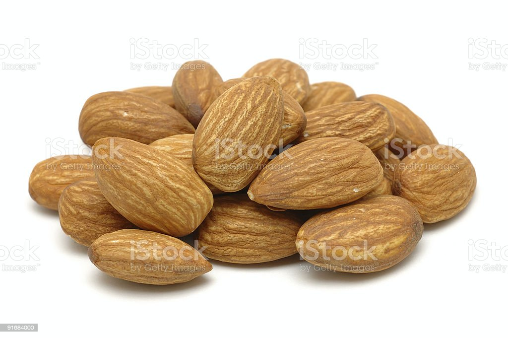 Pile of ripe brown almonds on a white background stock photo