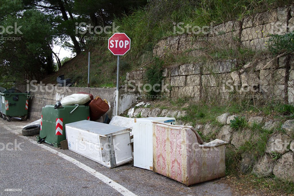 Pile of Roadside Trash around a red STOP sign stock photo