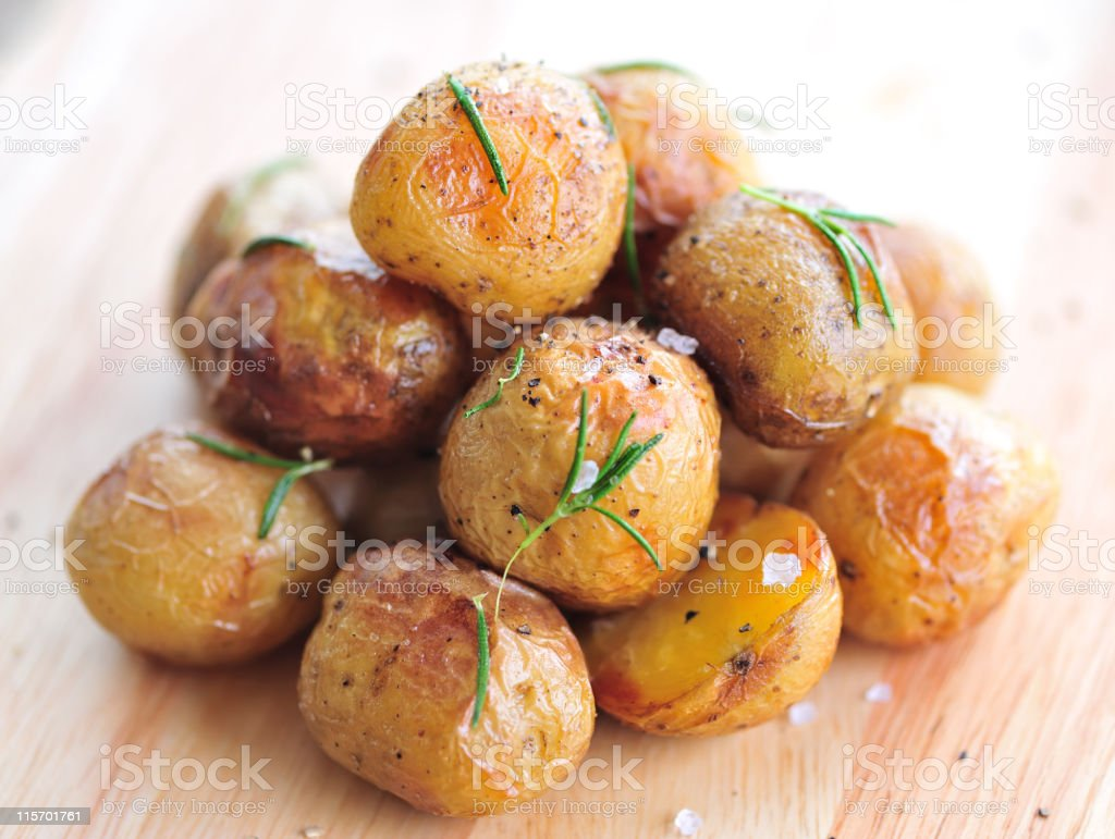 A pile of roasted young potatoes on a wooden table  stock photo