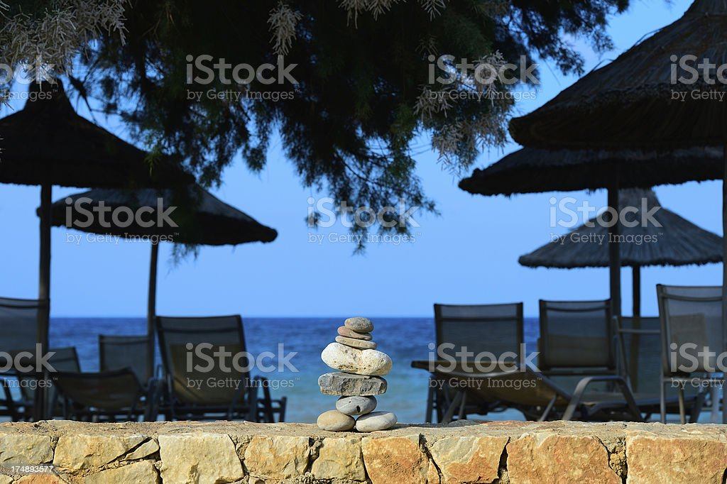 Pile of rocks on resort wall. Umbrellas and chairs. royalty-free stock photo