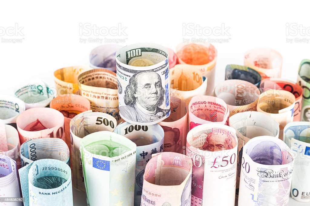 Pile of rolled-up currency notes with US Dollar on top stock photo