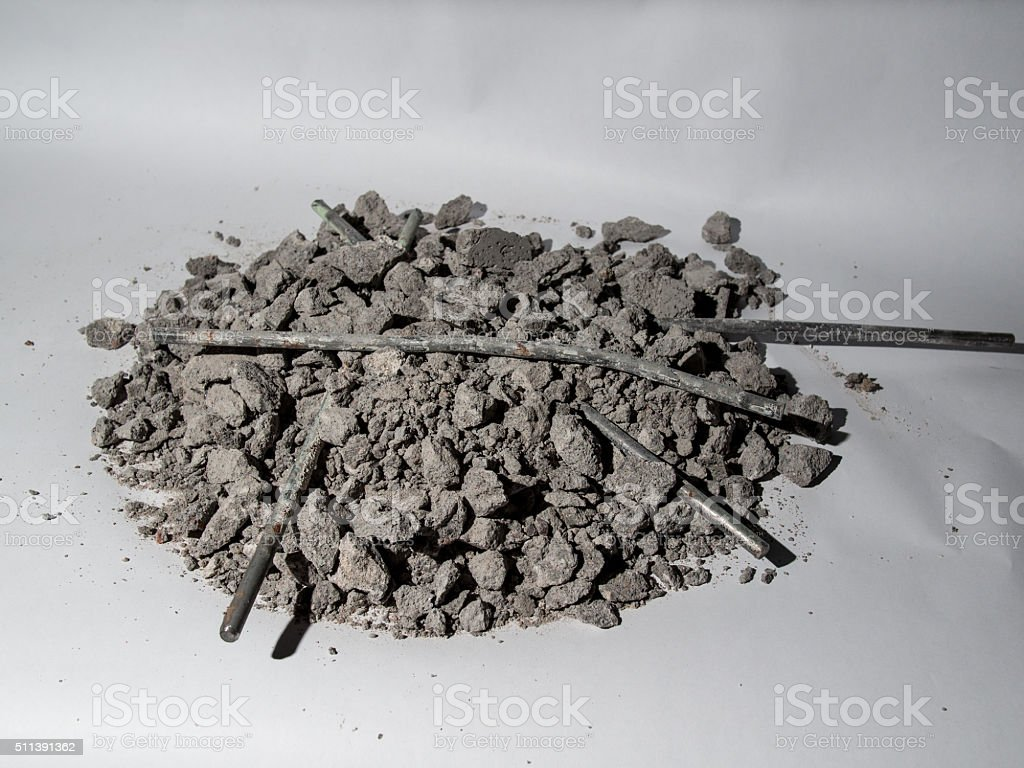 pile of ruined concrete with reinforcement against a dark background stock photo
