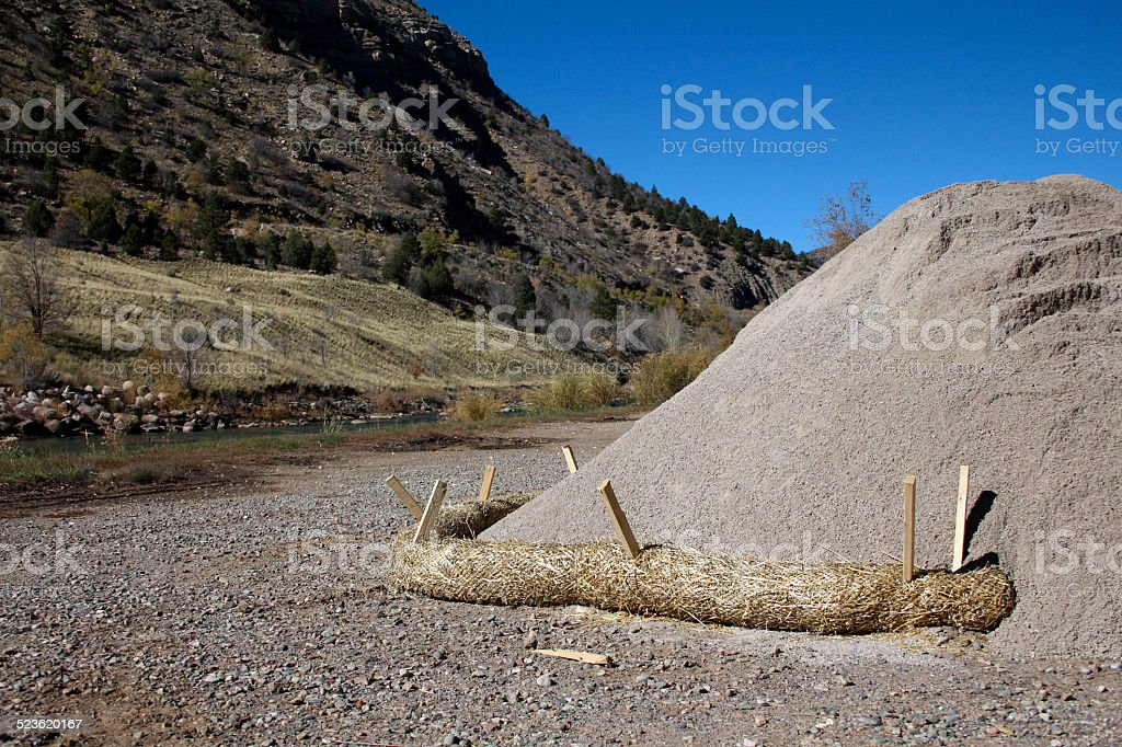 Pile of sand with a fiber roll by river stock photo
