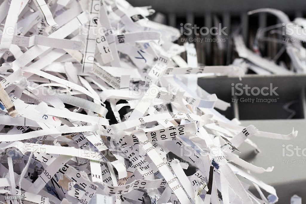 Pile of Shredded Paper with Shredder in Background stock photo