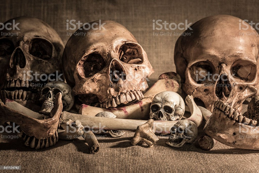 Pile of skulls and bones on sackcloth stock photo