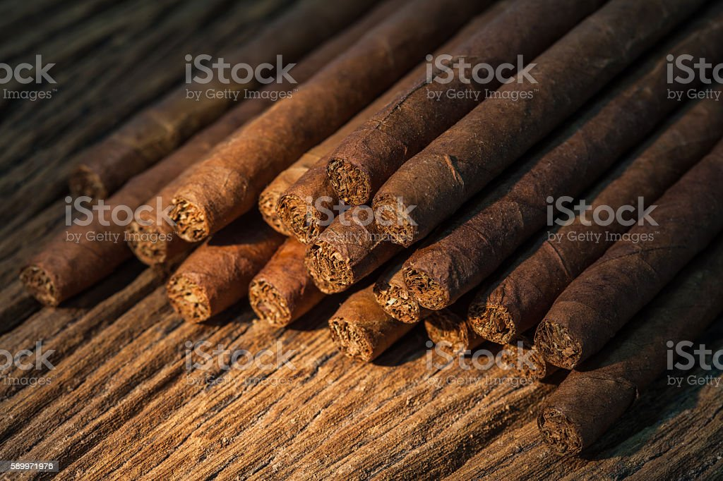 pile of small cigar on old wooden table stock photo