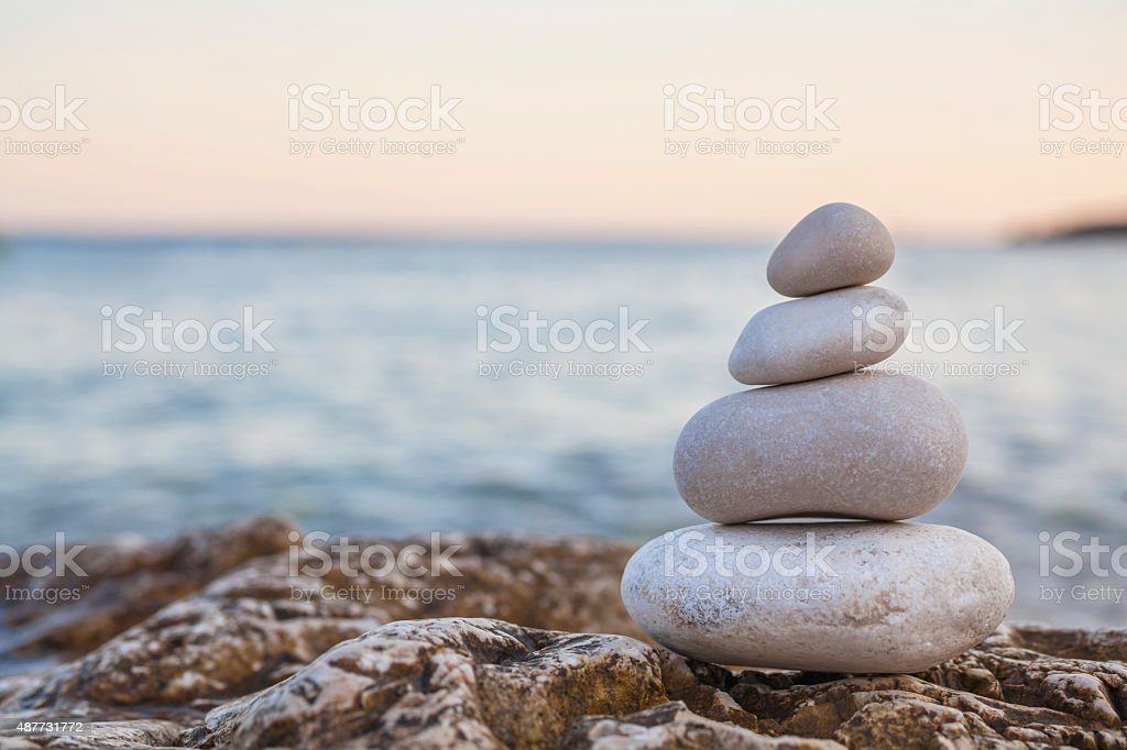 Pile of Stones on Tranquil Beach at Sunset stock photo