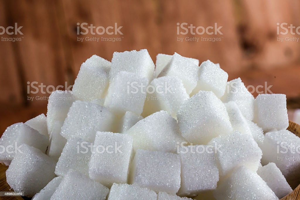 Pile of Sugar Cubes over Wooden Background stock photo