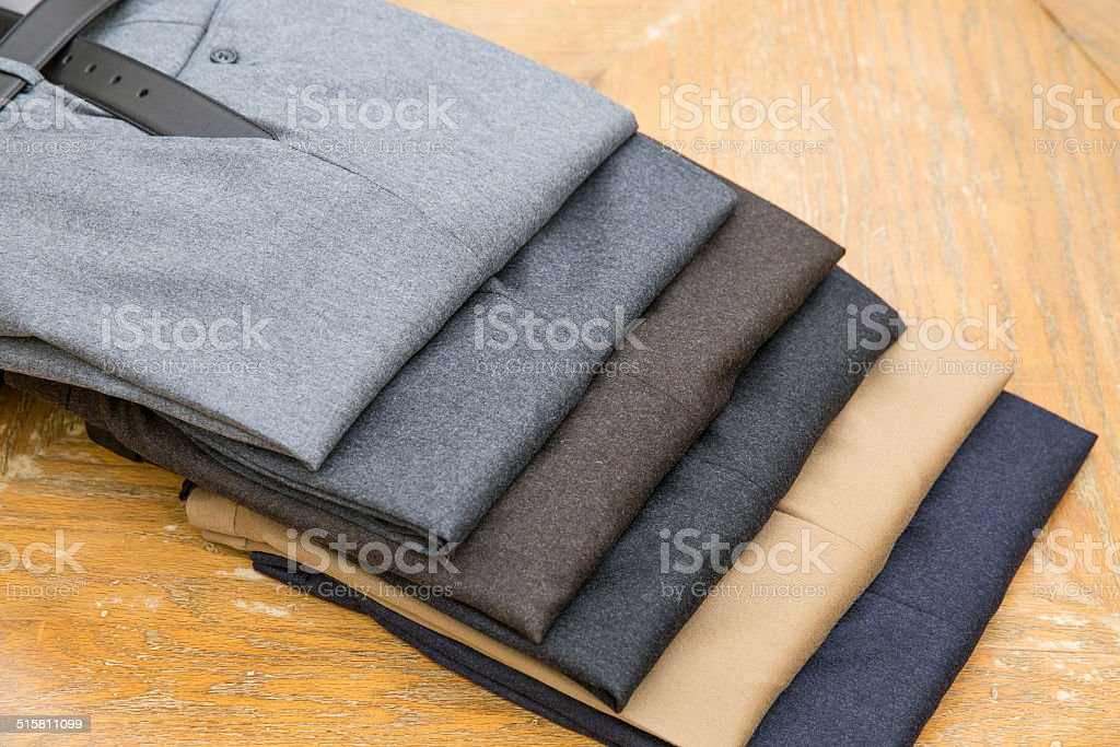 Pile of suit pants on wooden table stock photo
