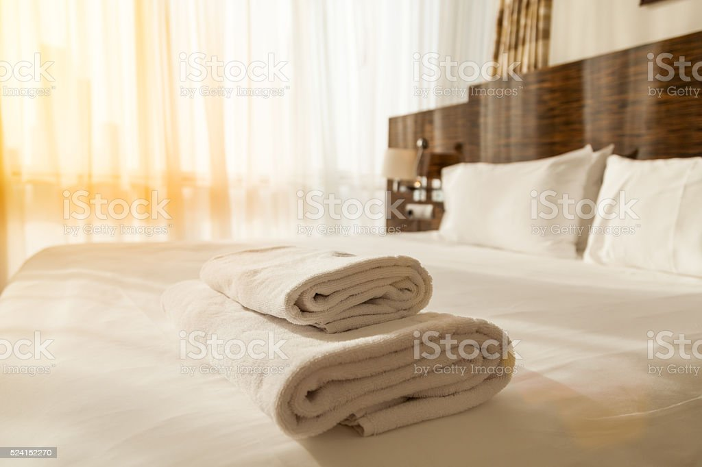 Pile of towels on the bed stock photo