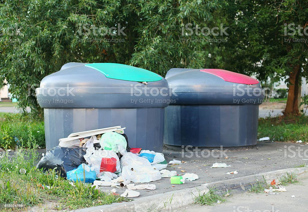 pile of trash scattered near the garbage cans on street stock photo