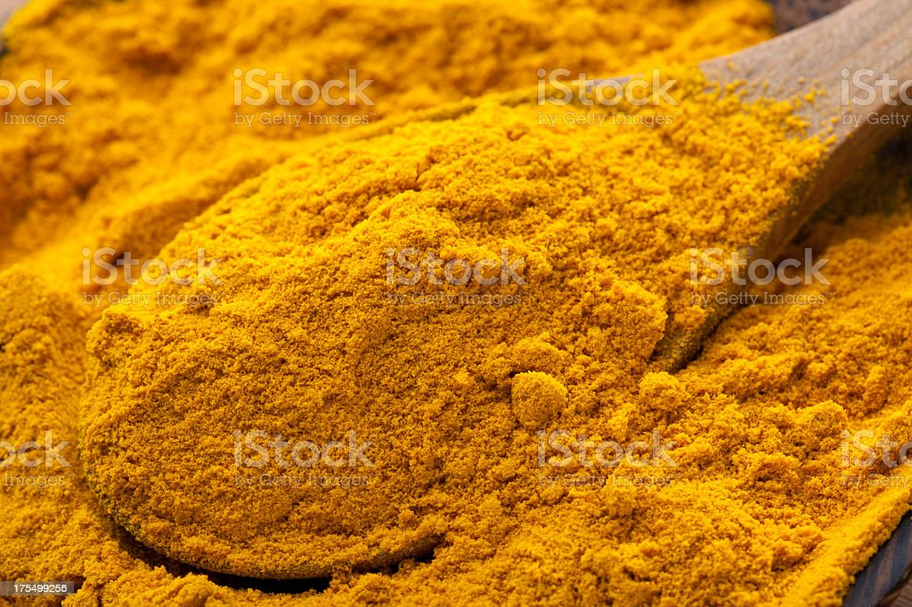 A pile of turmeric in a bowl with a wooden spoon stock photo