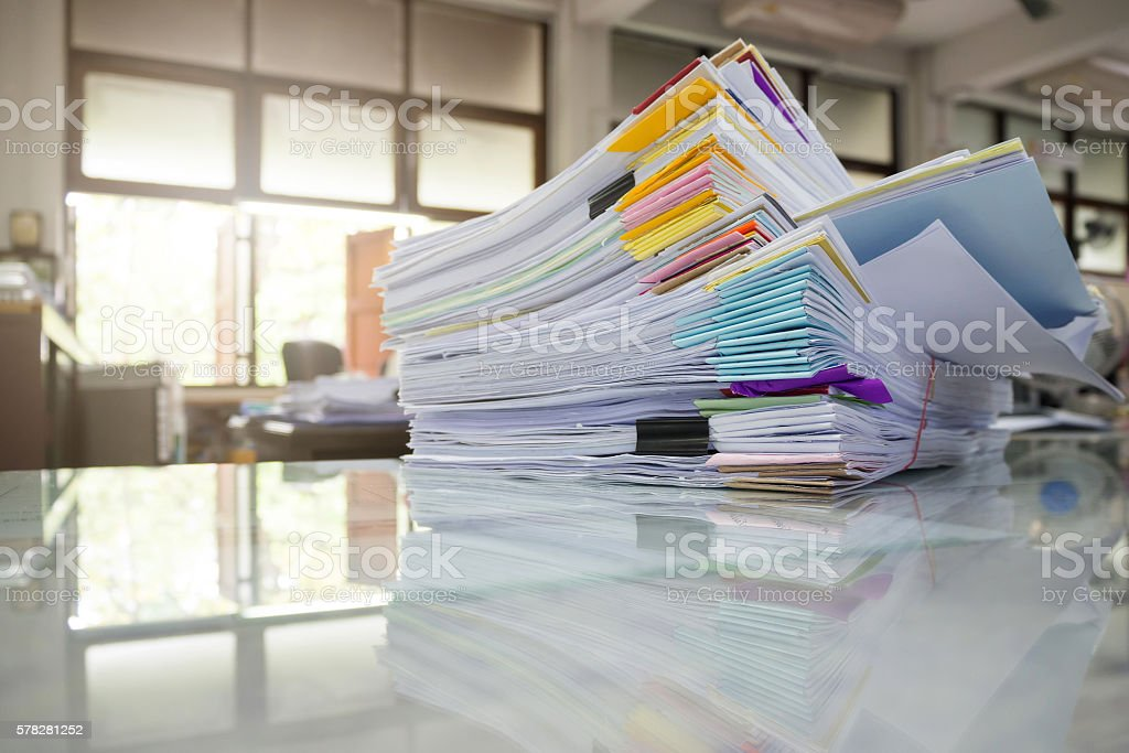 Pile of unfinished documents on office desk stock photo