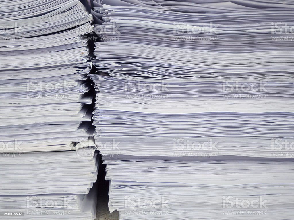 Pile of unfinished documents on office desk with businessman background stock photo