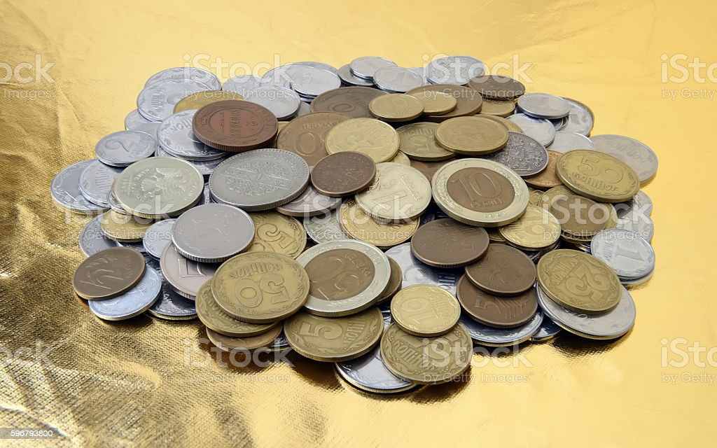Pile of various coins on a gold background stock photo