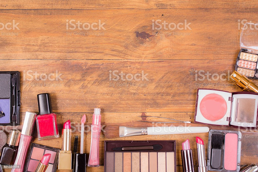 Pile of various cosmetics lie on wooden dressing table. stock photo