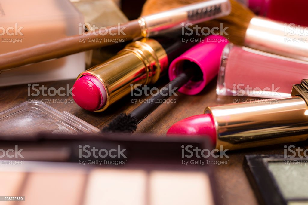 Pile of various cosmetics, make-up lie on wooden dressing table. stock photo
