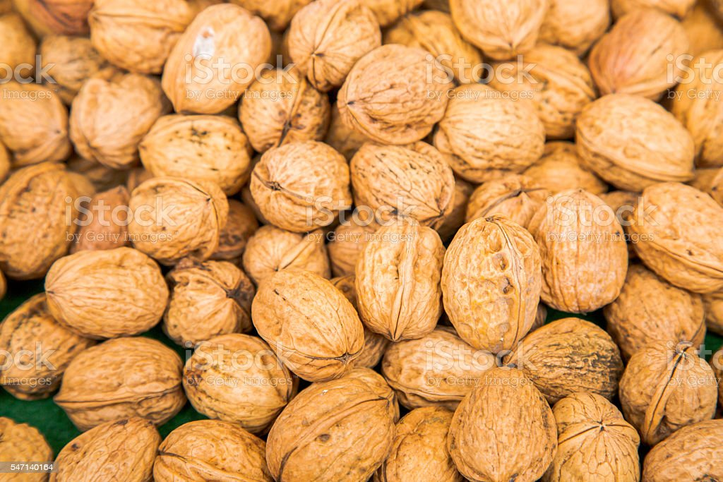 Pile of walnuts in their shells stock photo