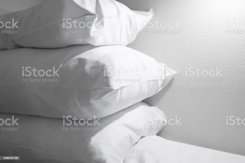 Pile of white pillows lying on empty bed stock photo