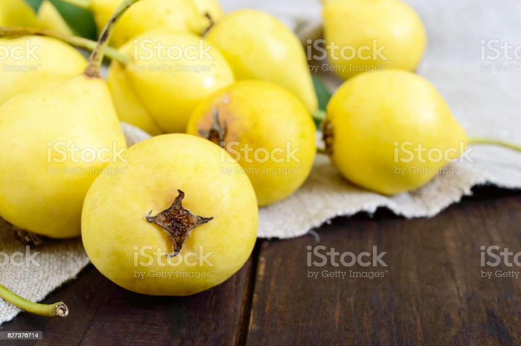 A pile of yellow pears scattered on a dark wooden table. Summer Ukrainian variety 'Limonka'. Close up stock photo