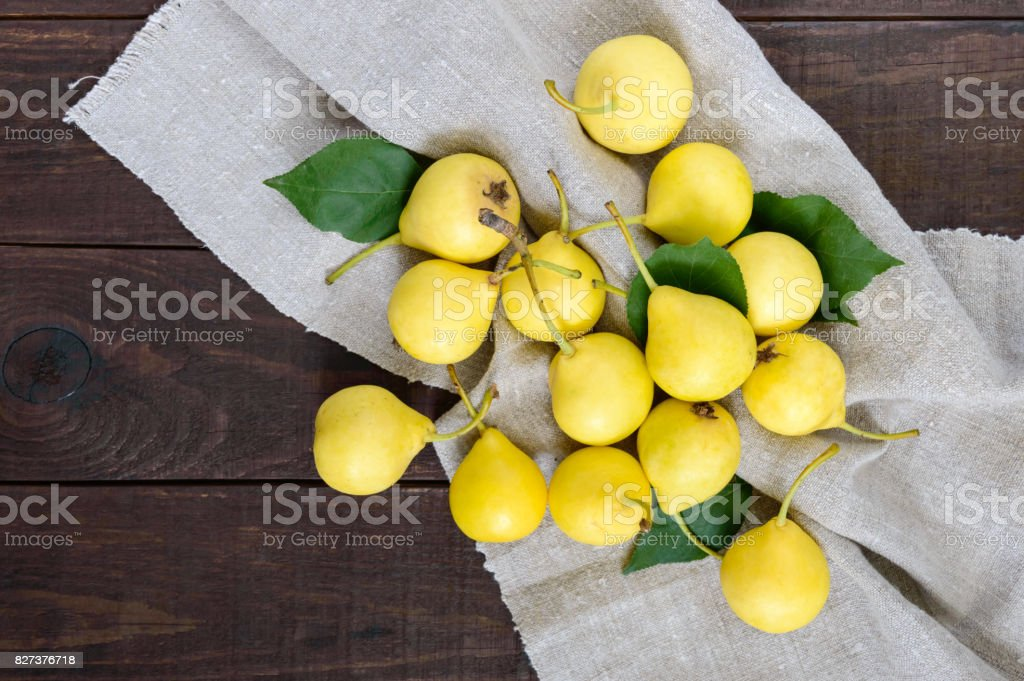 A pile of yellow pears scattered on a dark wooden table. Summer Ukrainian variety 'Limonka'. stock photo