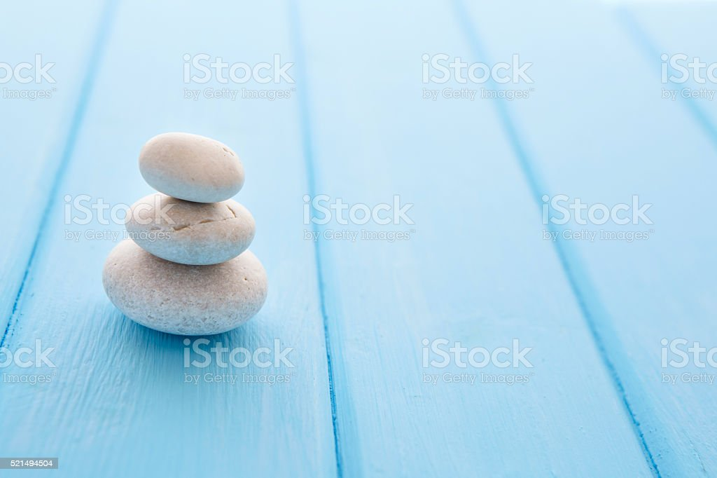 Pile planar stones on the old wooden rustic table. stock photo