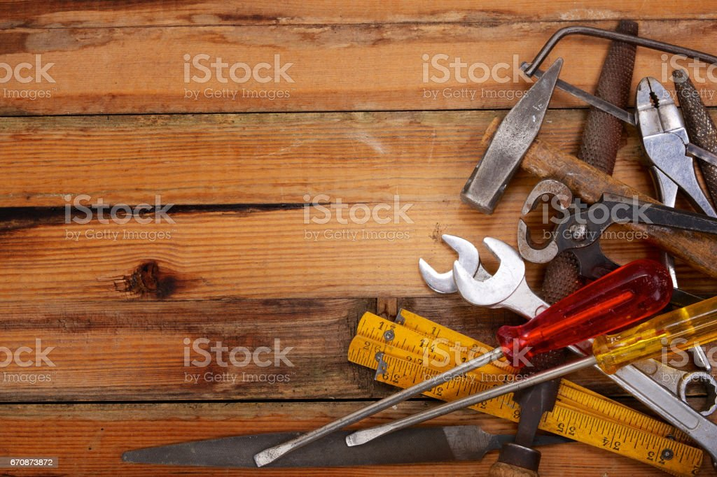 Piled hand tools on a wooden workbench stock photo