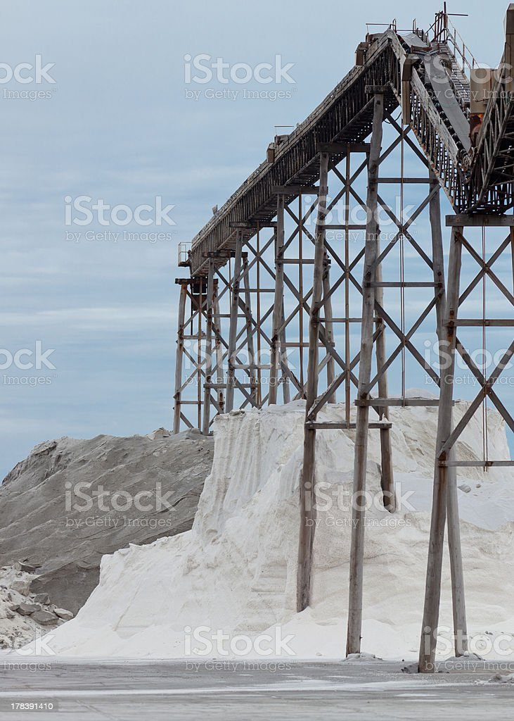 Piled sea salt under conveyor of saline refinery royalty-free stock photo