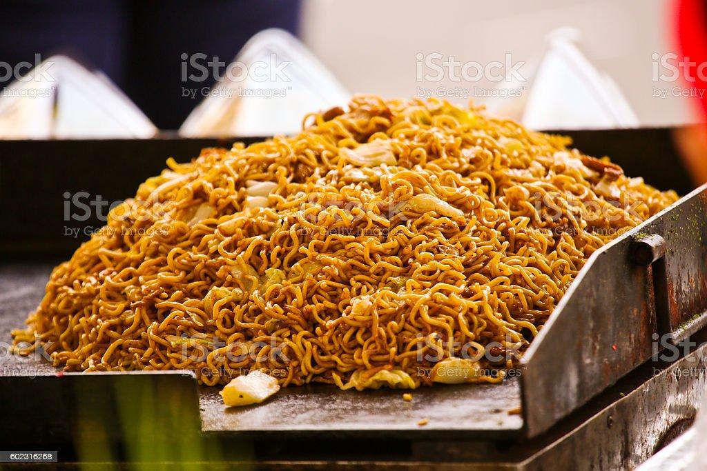 Piled yakisoba on griddle at a street food vendor stock photo