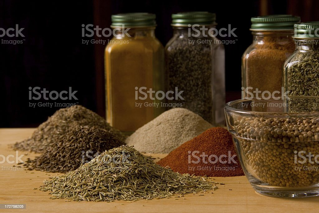 Piles and jars of various cooking spices stock photo