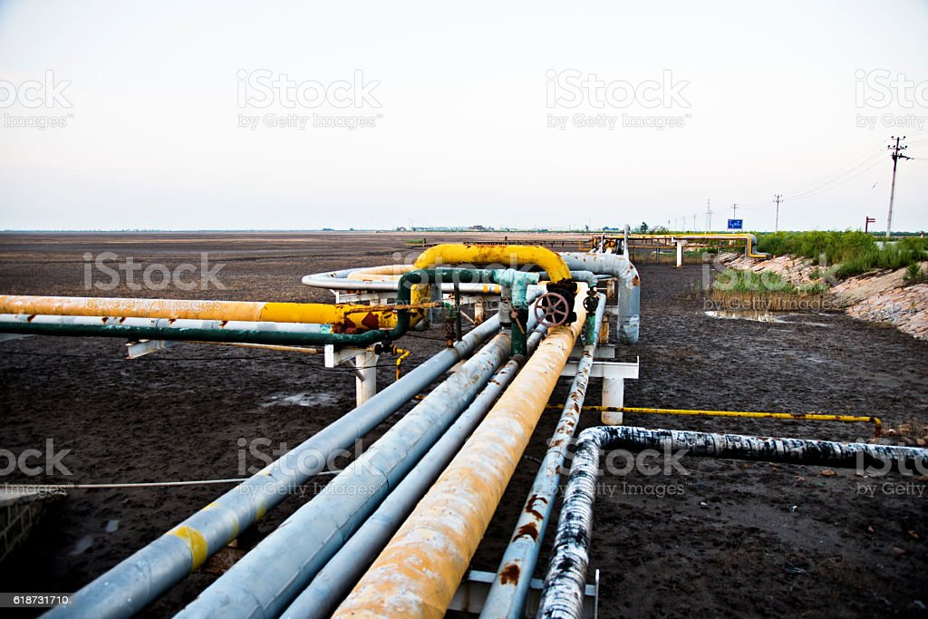 Piles going to oil refinery stock photo