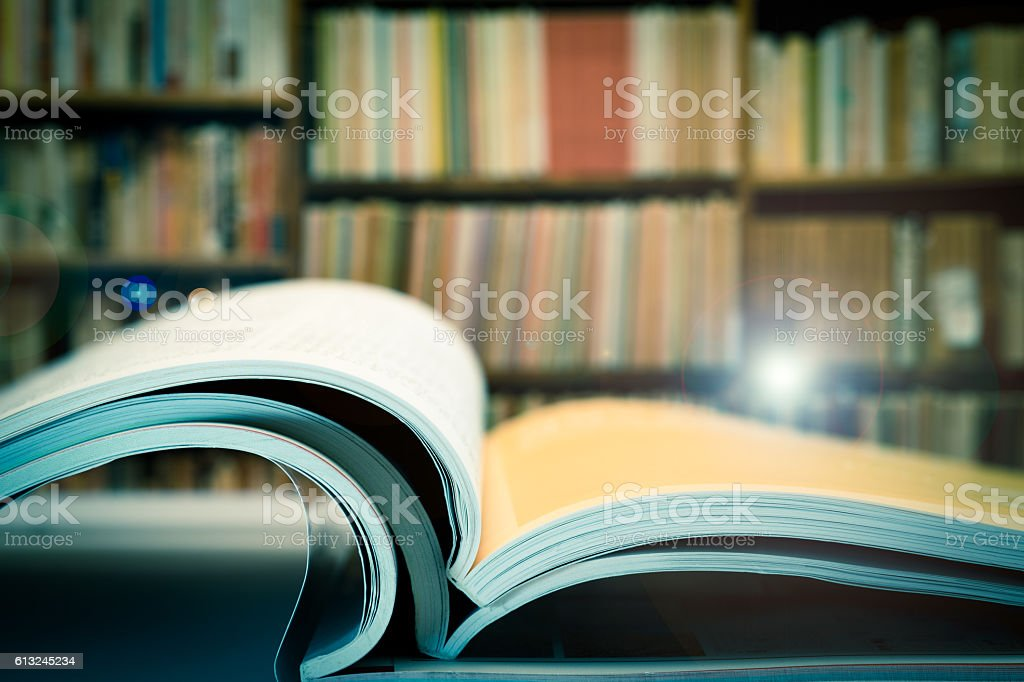 Piles of books and magazines on background of book shelf, with lens...