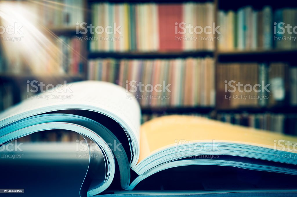 Piles of books and magazines on background of book shelf