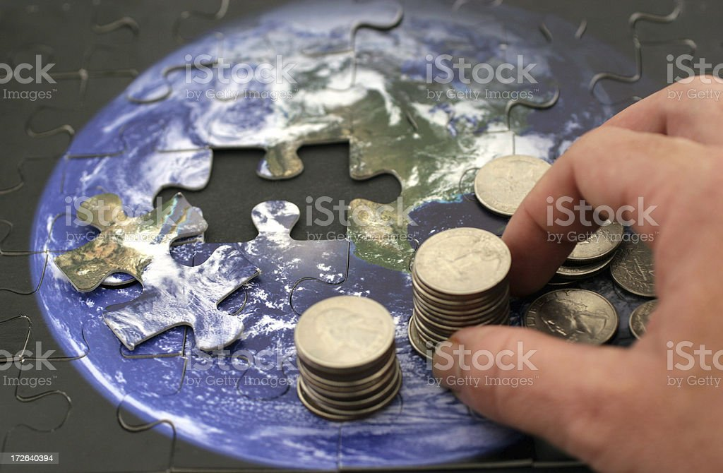 Piles of coins on top of a jigsaw puzzle of the Earth royalty-free stock photo