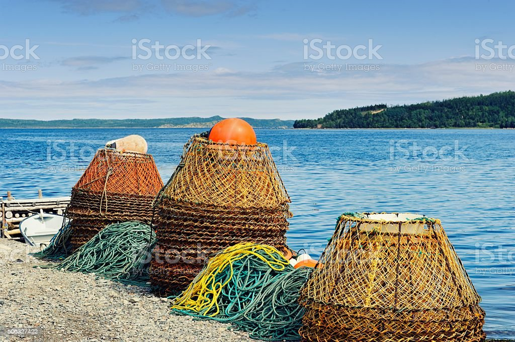 Piles of crab pots at the water's edge stock photo