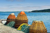 Piles of crab pots at the water's edge