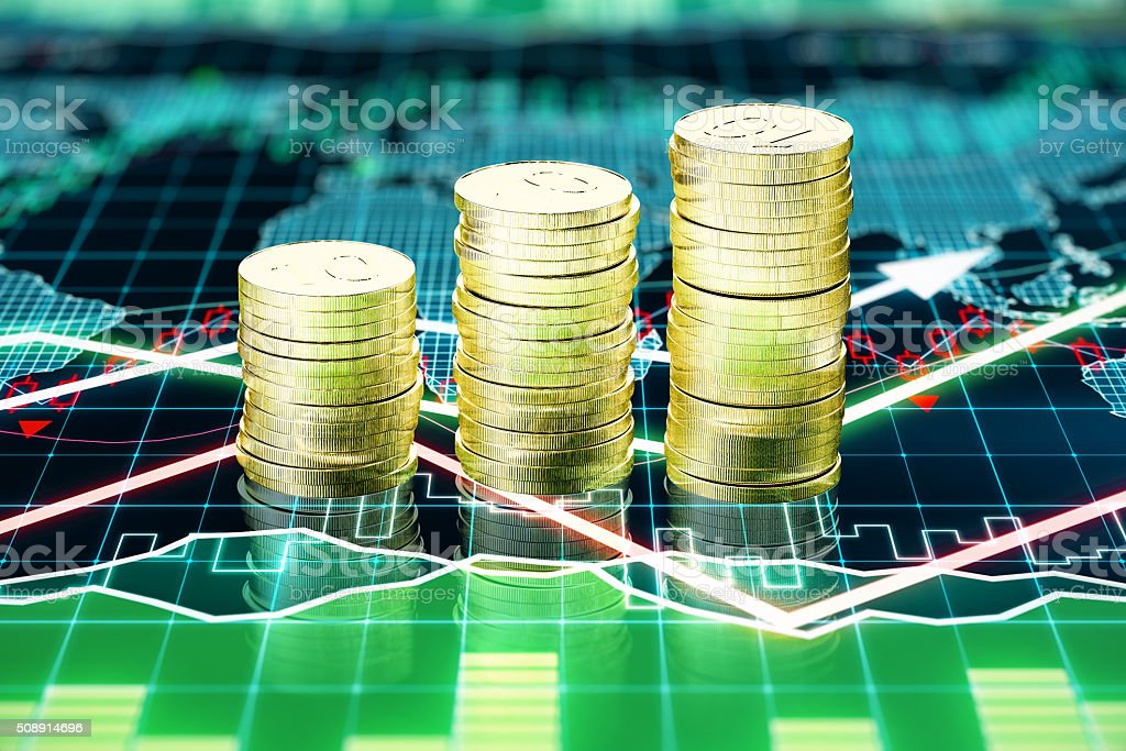 Piles of gold coins on the screen with business chart stock photo