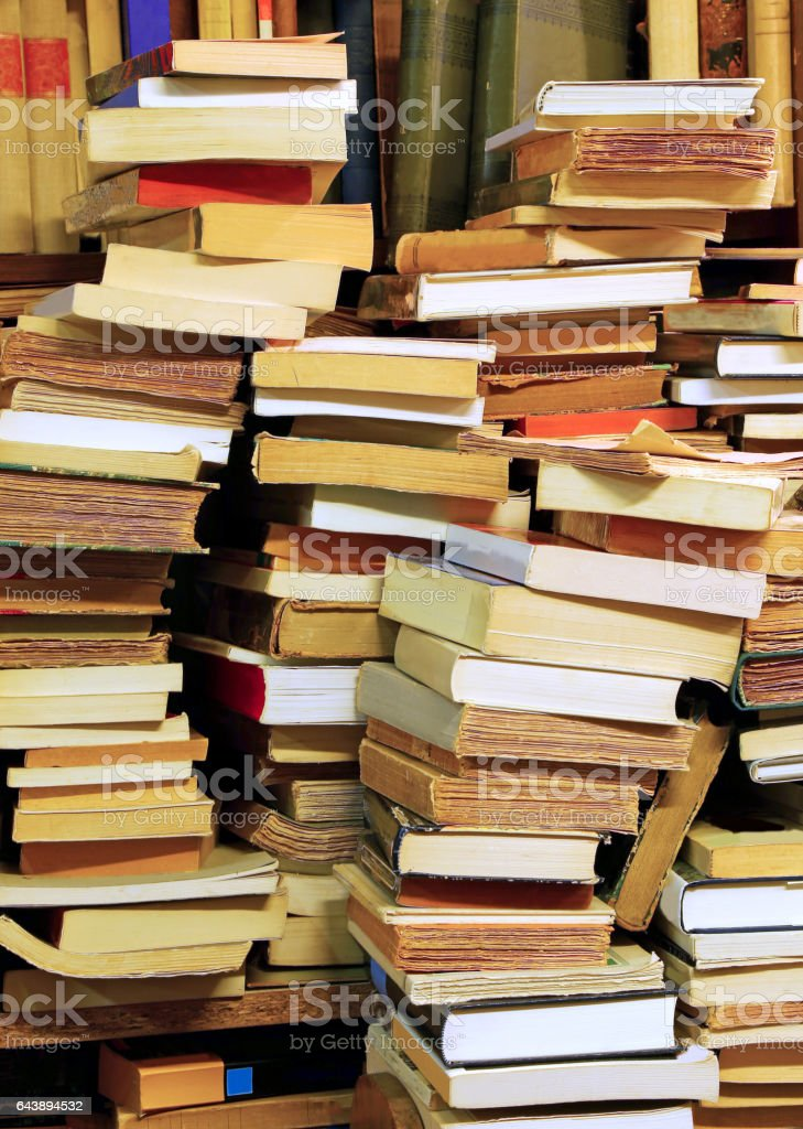 piles of old books for sale in a library stock photo