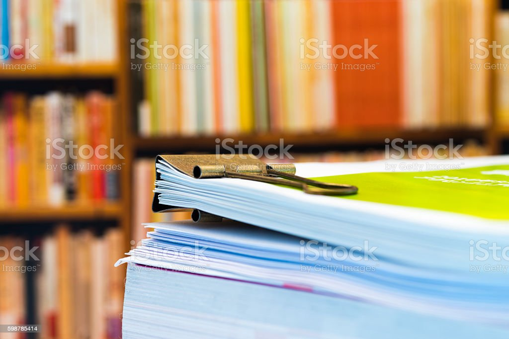 Piles of paper on background of book shelf stock photo