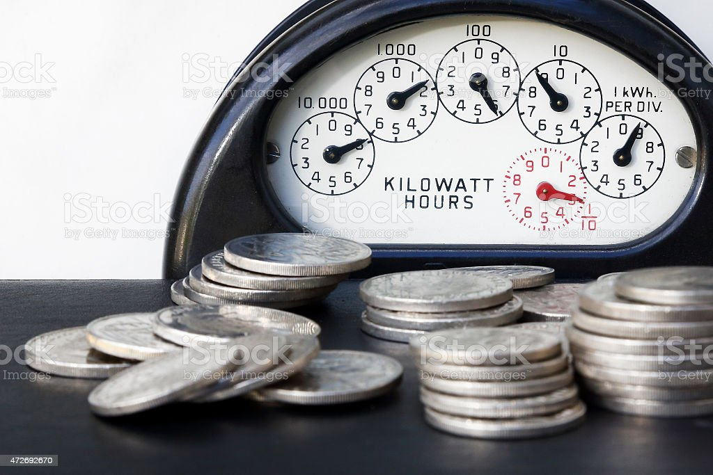 Piles of silver coins in front of an electricity meter stock photo