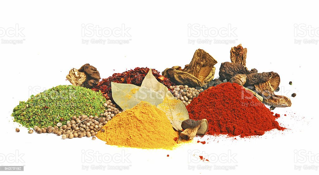 Piles of spices in many colors with some leaves and seeds stock photo