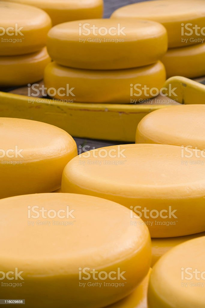 piles of waxed yellow cheeses royalty-free stock photo