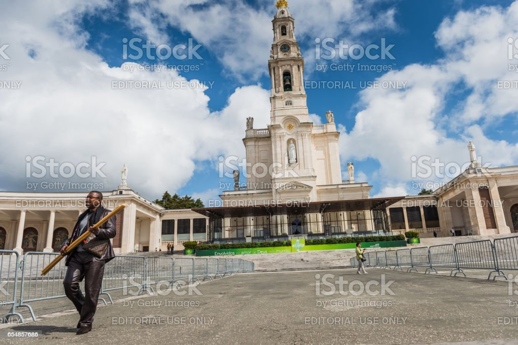 Pilgrim carries a huge candle, The Sanctuary of Fátima, Portugal stock photo