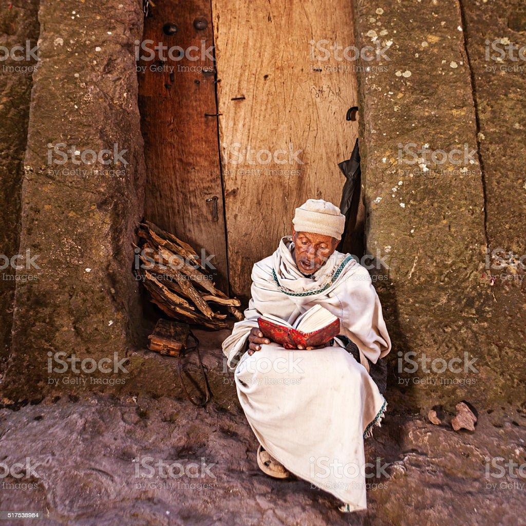 Pilgrim reading the holy book near one of Lalibela's churches stock photo