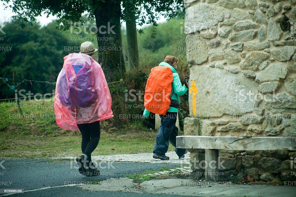 Pilgrims in the 'camino de Santiago', yellow arrow. stock photo
