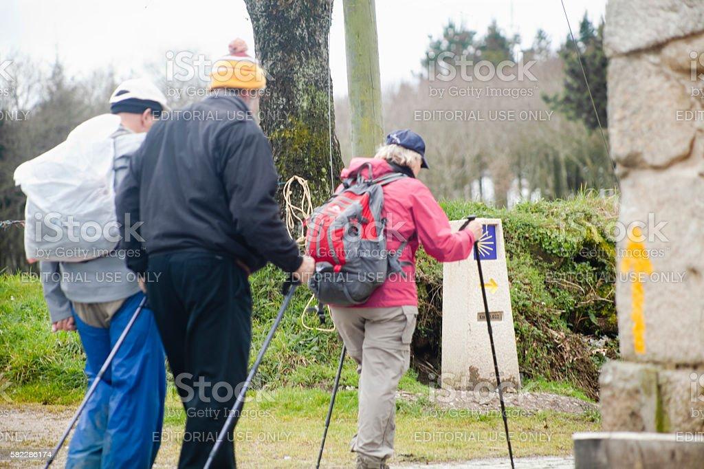 Pilgrims in the 'camino de Santiago', yellow arrow sign. stock photo