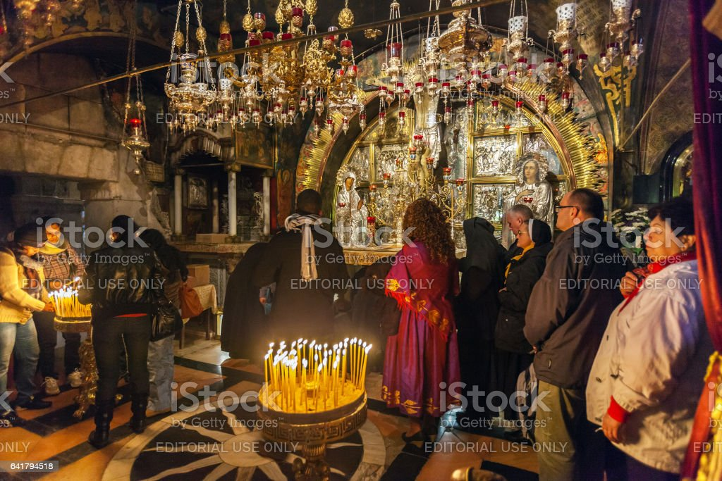 JERUSALEM, ISRAEL - FEBRUARY 16, 2013: Pilgrims praying near Golgotha Mountain in Temple of Holy Sepulchre stock photo