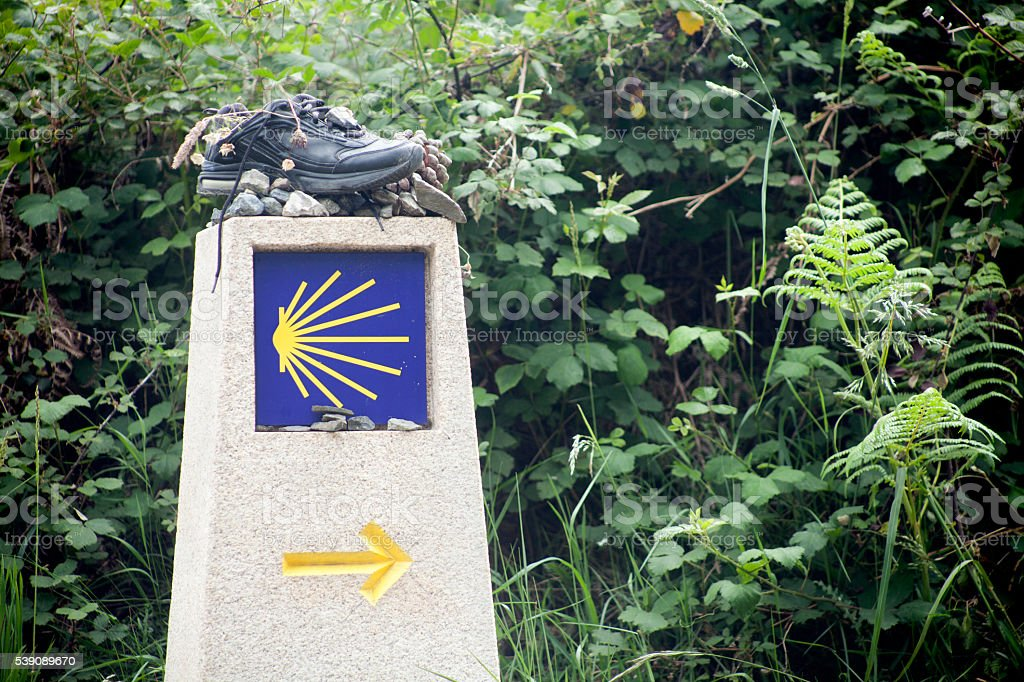 Pilgrims shell and old boot in the Camino de Santiago stock photo