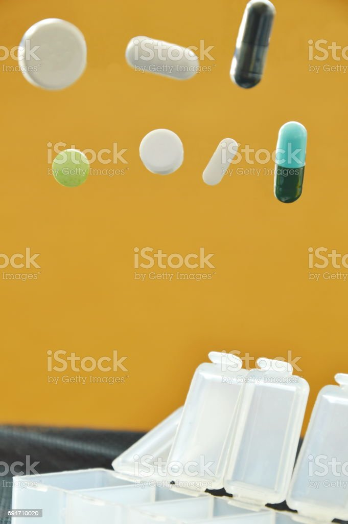 pill and capsule dropping to plastic box stock photo